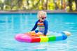 Leinwanddruck Bild - Child on inflatable float in swimming pool.