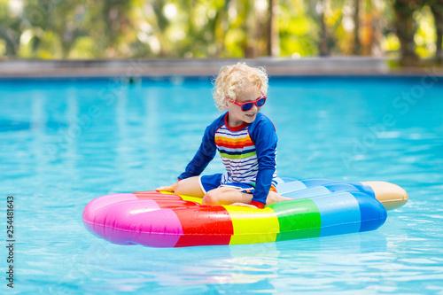 Leinwanddruck Bild Child on inflatable float in swimming pool.