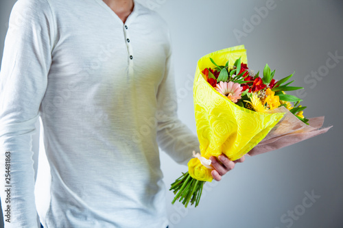 man hand holding flowers bouquet
