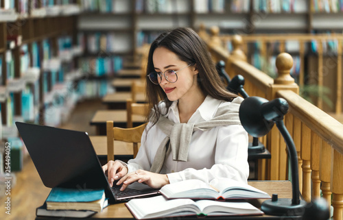 Pretty female student with laptop and books working in a high school library