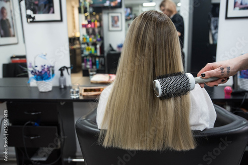 Professional hairdresser brushing beautiful client's hair with round brush