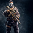 Private security service contractor wearing a balaclava skull holding an assault. Studio photo against a dark textured wall