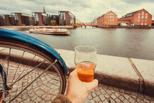 obraz PCV Beer glass of drinker and cityscape, water channel, old buildings of Copenhagen, Denmark. Danish capital with cycles, houses and tourists