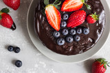 Cheesecake with raisin decorated with chocolate glaze and fresh strawberries and blueberries.