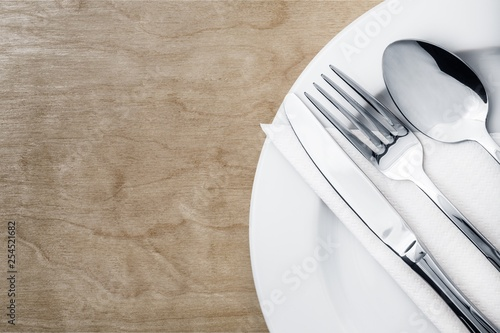 Fork, spoon and knife on plate on wooden background