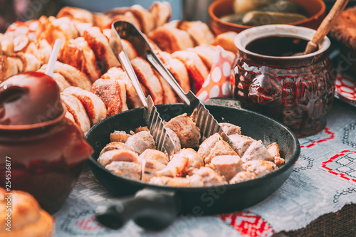 Dishes of the traditional Belarusian cuisine - fried bacon and meat sausages, pastries. © Grigory Bruev