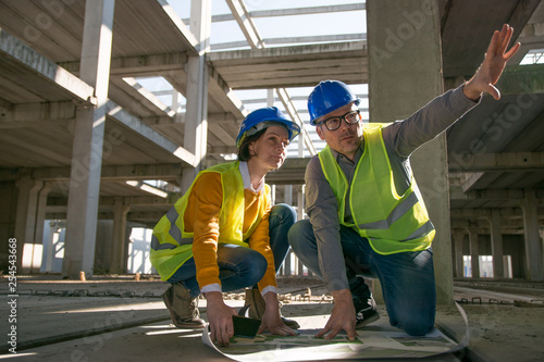 Two architects kneeling on the floor and discussing over blueprint