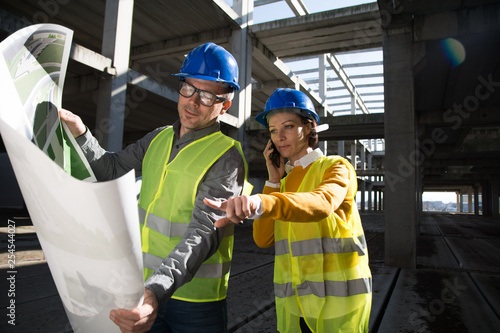 Two young architects on a construction site, discussing project details