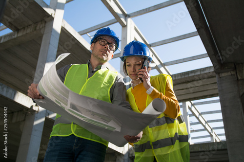 Two young architects checking blueprint