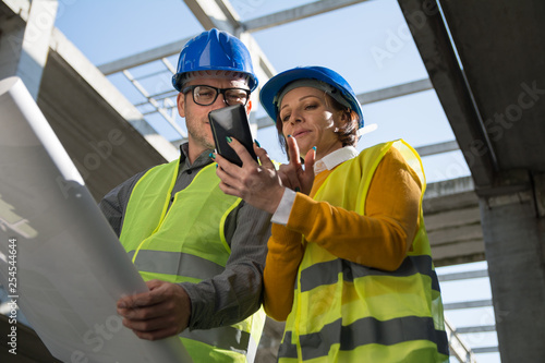 Female architect showing blueprint on her mobile phone to her colleague