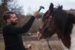uomo si prende cura della criniera del suo cavallo