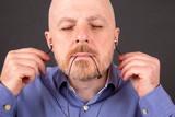 bearded man wants to listen to music through vacuum headphones