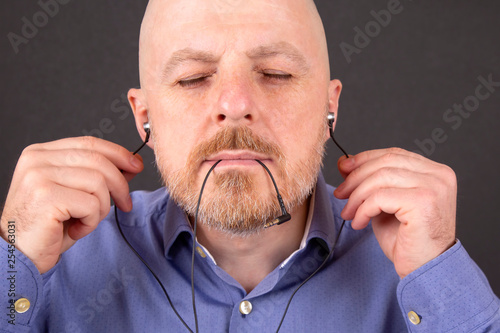 bearded man wants to listen to music through vacuum headphones - 254563031