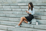 Portrait of a young beautiful student sitting on the steps of the University outdoors with a tablet and headphones and coffee