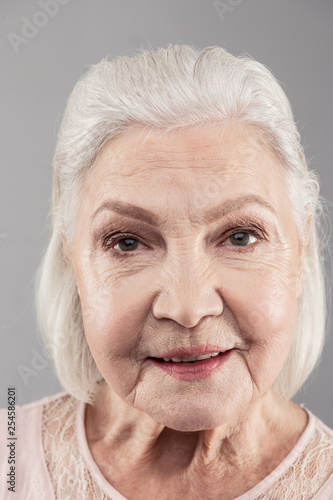 Old grey-haired woman with bob haircut looking directly into camera