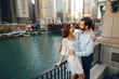 beautiful long-haired girl in summer dress with her handsome husband in white shirt and pants standing in sunny Chicago near river
