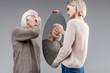 Impressed old lady closing her eyes while looking in mirror
