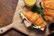 Leinwandbild Motiv Croissants catering Croissant sandwiches orange juice served wooden board
