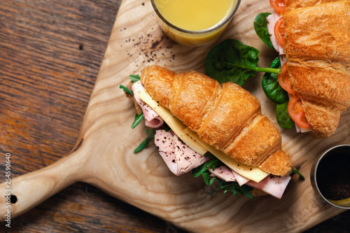 Leinwanddruck Bild Croissants catering Croissant sandwiches orange juice served wooden board