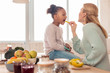 Blonde-haired mother feeding her cute funny girl with fruits