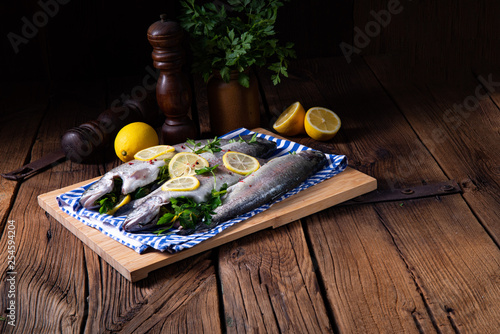 Leinwanddruck Bild fresh trout with lemon and different herbs