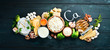 Products containing natural calcium: cheese, milk, parmesan, sour cream, fish, almonds, parsley, garlic, broccoli. On a black wooden background. Top view. Free copy space.