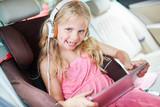 Mädchen im Auto mit Kopfhörer und Tablet