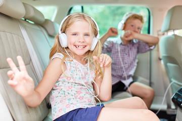 Glückliche Kinder singen zur Musik im Auto