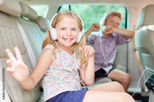 Glückliche Kinder singen zur Musik im Auto - 254619414