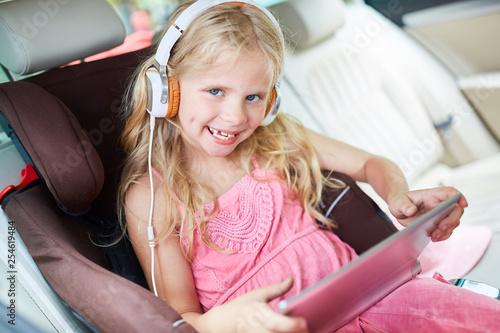 Mädchen im Auto mit Kopfhörer und Tablet - 254619484