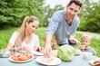 Familie mit Kindern beim Essen im Garten