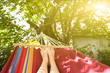 Leinwanddruck Bild - Fit girl is lying in the colourful hammock. Woman with beautiful legs is relaxing in hippie style garden near the village house. Rustic holidays concept.