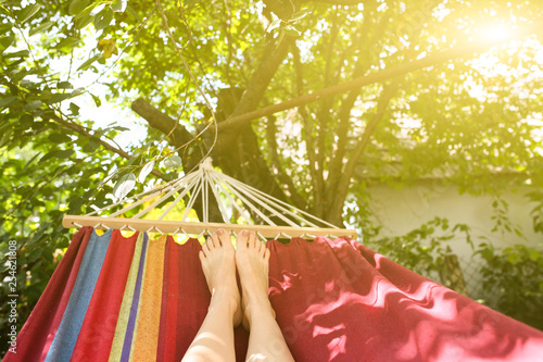 Leinwanddruck Bild Fit girl is lying in the colourful hammock. Woman with beautiful legs is relaxing in hippie style garden near the village house. Rustic holidays concept.