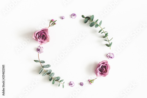 Flowers composition. Wreath made of eucalyptus branches and rose flowers on white background. Flat lay, top view, copy space - 254622061