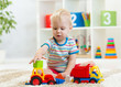 Leinwandbild Motiv Nursery baby boy playing with toy cars in kindergarten
