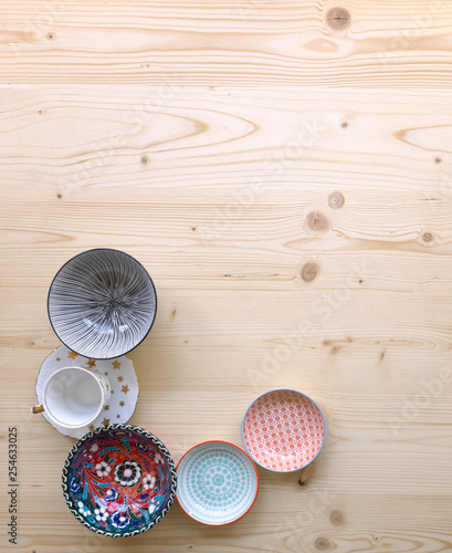different kinds of modern colourful crockery in different designs on light wood background - 254633025