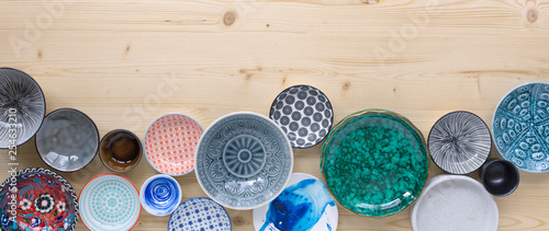 different kinds of modern colourful crockery in different designs on light wood background - 254633210