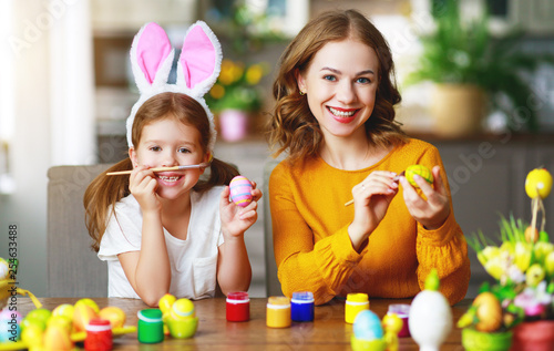 Happy easter! family mother and child with ears hare getting ready for holiday.