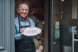 Cheerful gentleman standing in the doorway of cafe and holding open sign