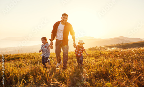 happy family father and children in nature at sunset.