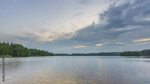 Timelapse of clouds over forest lake at sunset