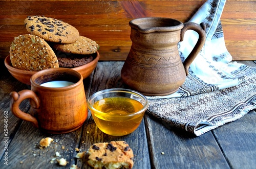 Oatmeal cookies in a ceramic rustic plate, milk in a ceramic mug, napkin, honey on a rustic wooden table. © YUABOG