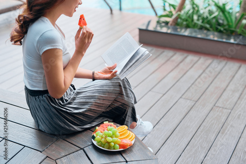 Portrait of pretty cheerful woman relax and reading book in vacation on summer season at resort swimming pool