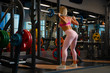 Leinwanddruck Bild - Photo from back of athlete girl crouching with barbell on her shoulders in gym.