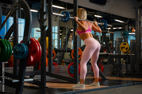 Leinwanddruck Bild Photo from back of athlete girl crouching with barbell on her shoulders in gym.