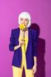 Leinwanddruck Bild - Pensive girl in white wig sniffing flower on purple background