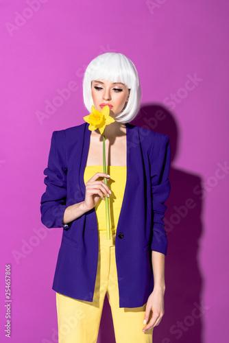 Leinwanddruck Bild Pensive girl in white wig sniffing flower on purple background