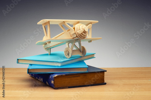travel for education or study abroad concept, retro airplane on stack of book over dark background
