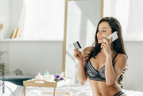Leinwanddruck Bild attractive woman holding credit card while talking on smartphone near tray with breakfast
