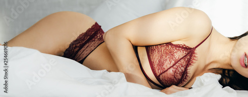 Leinwandbild Motiv panoramic shot of sexy young woman in red lingerie lying in bedroom